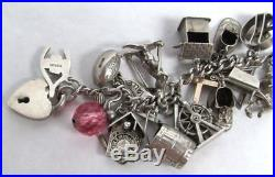 CIRCA 1930's STERLING SILVER CHARM BRACELET WITH 31 ANTIQUE CHARMS